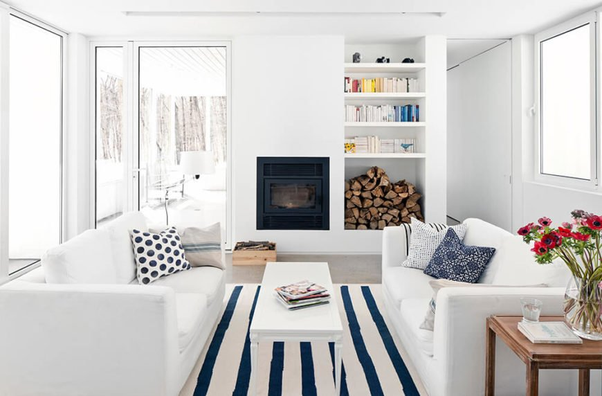 The living room ends with a fireplace built into the wall, plus an adjacent shelving and storage alcove that holds both books and a supply of firewood.