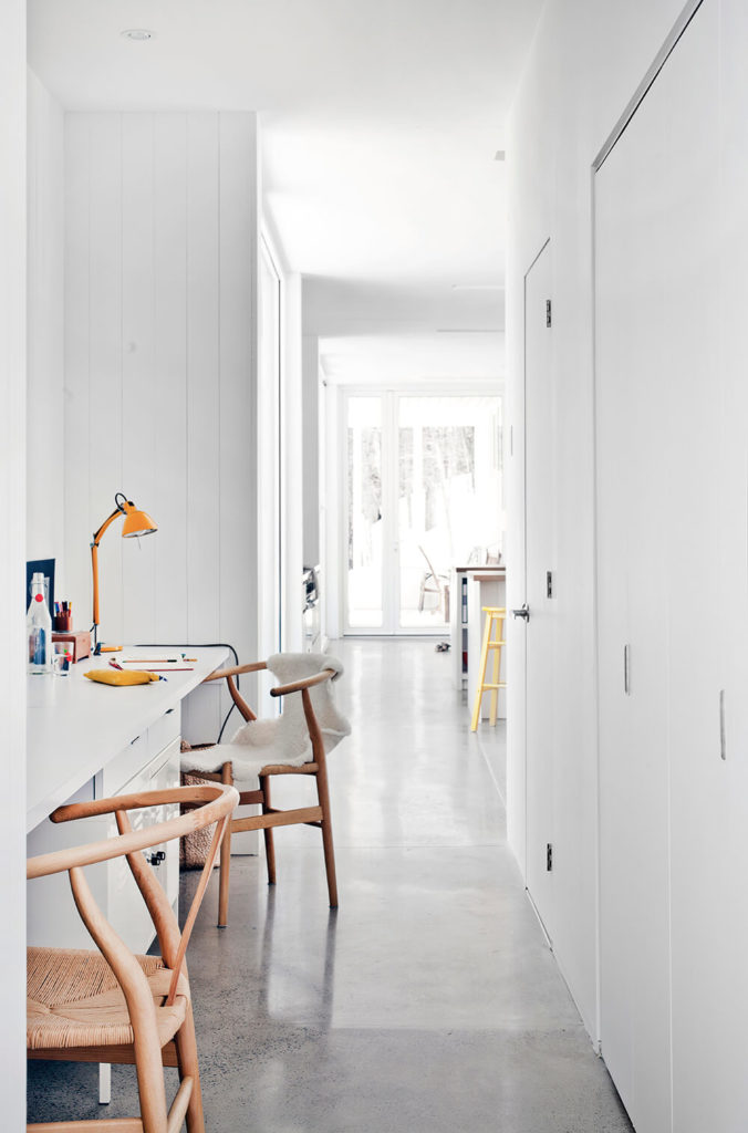 Extending from the central open space, this hall leads to the private areas of the home, bedrooms and bathrooms. A slim desk is built into the alcove at left for convenient work space.