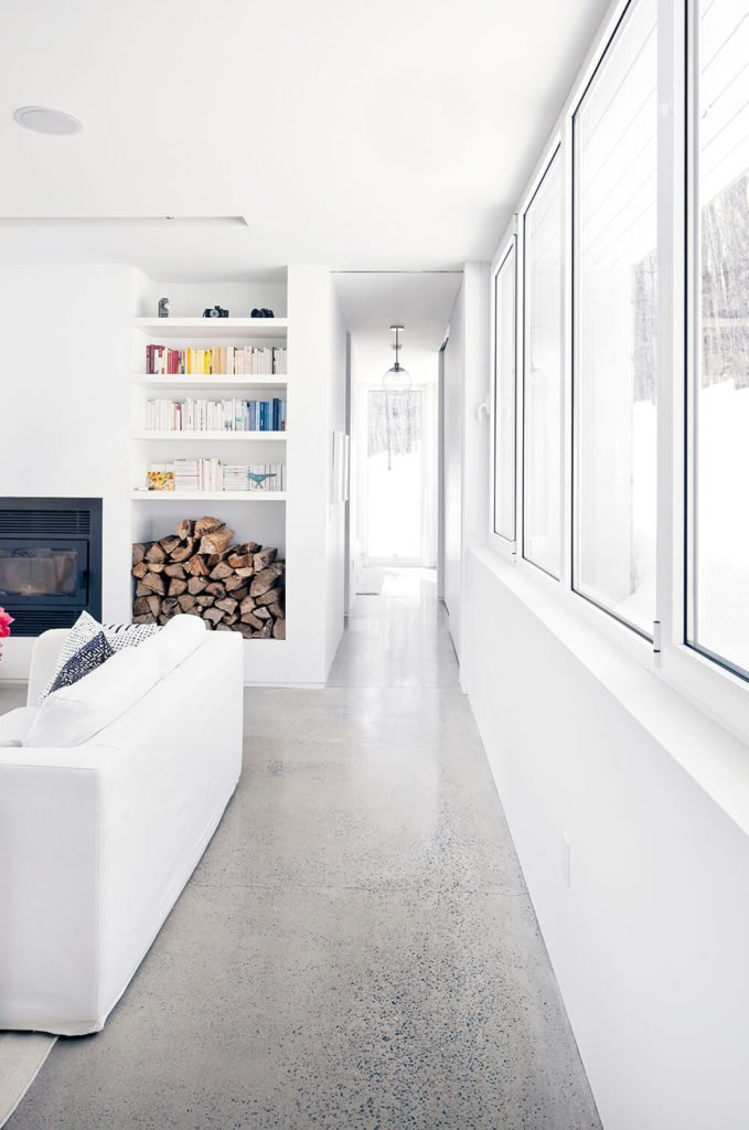 Past the set of broad windows, we can see a hallway extending toward the bedrooms. The polished concrete flooring connects and unifies every disparate end of the home.