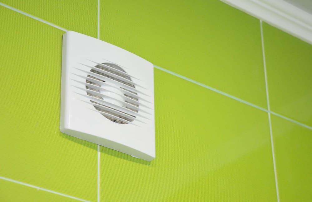 A white smart exhaust fan on a green wall.