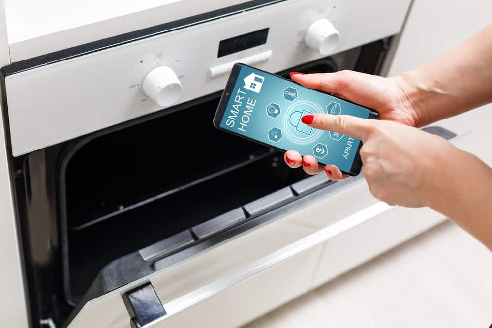 A woman sets up her oven with an app on her phone.