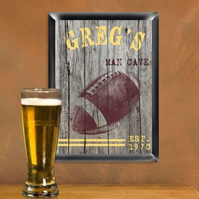 """We love the idea of hanging up cheeky """"man cave"""" signs in the man cave, a knowing wink to the boys' room history of the space. It's always great when wall decorations combine a couple passions. In this case, we see a football themed sign done up in antique textures for a rustic, old fashioned appearance. This one can be personalized with up to 15 characters at the top and 30 characters below."""