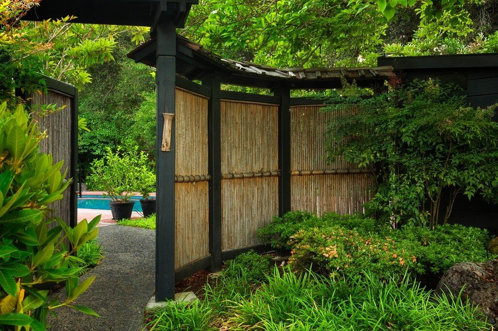 A curved fence with lacquered black supports has a large gate that opens up to expose the backyard, complete with a beautiful aqua pool. The forested lot has plants growing right up to the fence, embracing the natural look favored by Japanese gardens.