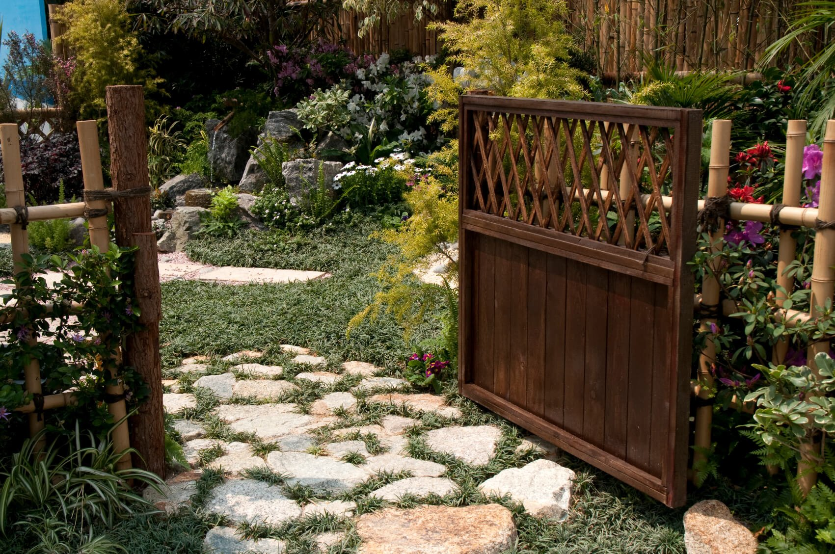 "This decorative ""picket"" bamboo is attached to a dark stained solid wood gate and terminal posts, providing access to the lush back garden via a slightly overgrown flagstone pathway."