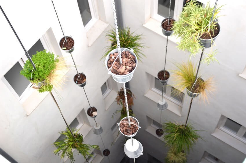 23-vertical-garden If your space is limited, hanging plant potters down shafts and in atriums makes good use of an area not thought to have much utility.