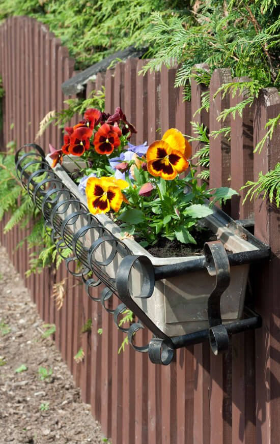 3-vertical-garden Wrought-iron flower pot holders help add a dash of style to the normally mundane business of potting your flowers.