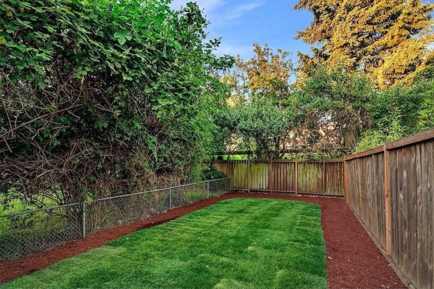 Here's an interesting take on a chain link fence. The whole of the property is surrounded by a tall wooden privacy fence, but divided down the middle with a much shorter chain link fence to denote separate outdoor living areas.