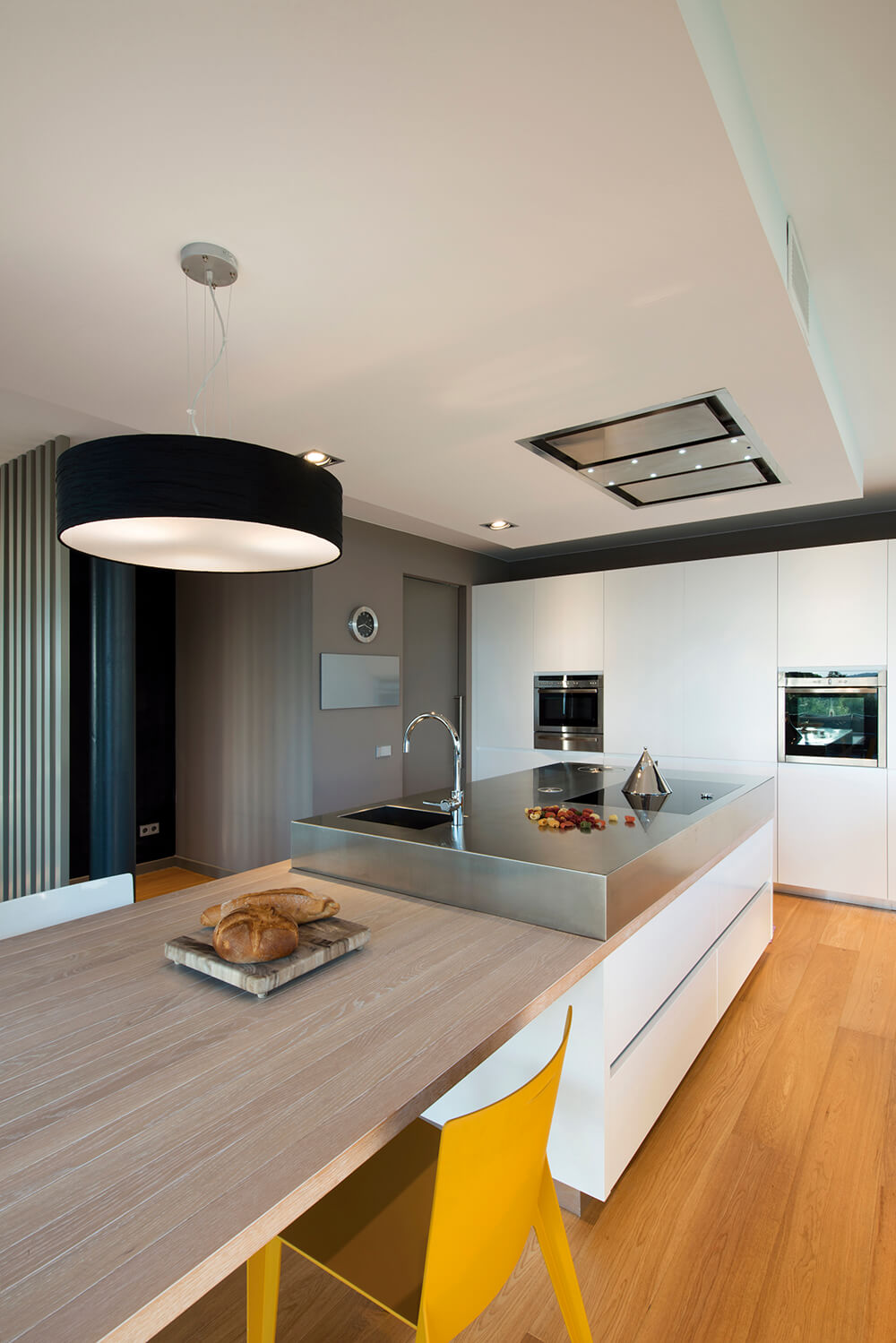 A closer view of the island and dine-in extension shows the different materials that exist in the kitchen. The floor consists of rich wood grain, the cabinetry a sleek white surface, while the top of the island transitions from a faded wood grain to a chrome surface