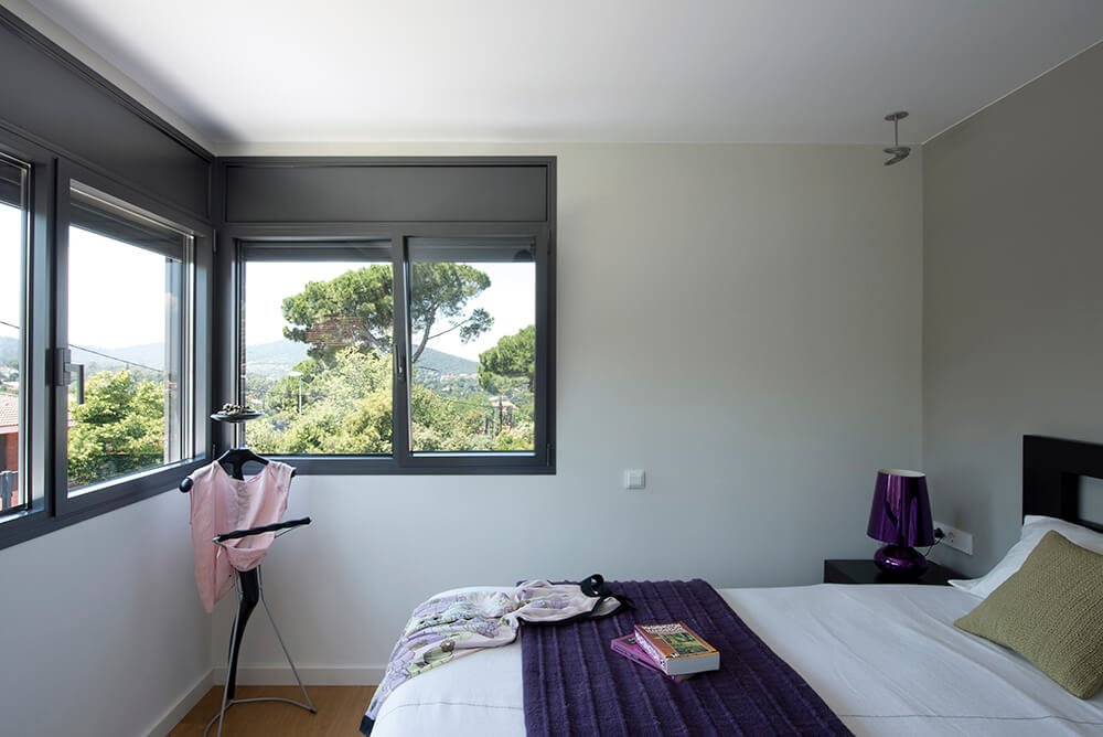 In the upper level of the home contains this bedroom. The modest space is personable and accented by the deep purple lamp and bed covers. More windows round the corner in this room and provide a view of the surrounding landscape.