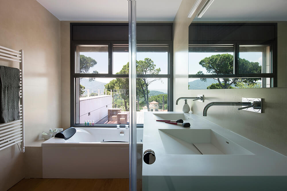 The bathroom is located right next to the bedroom. The large sinks and surplus of counter space allows for this space to accommodate a variety of different needs. The luxurious bath sits just below a large window.