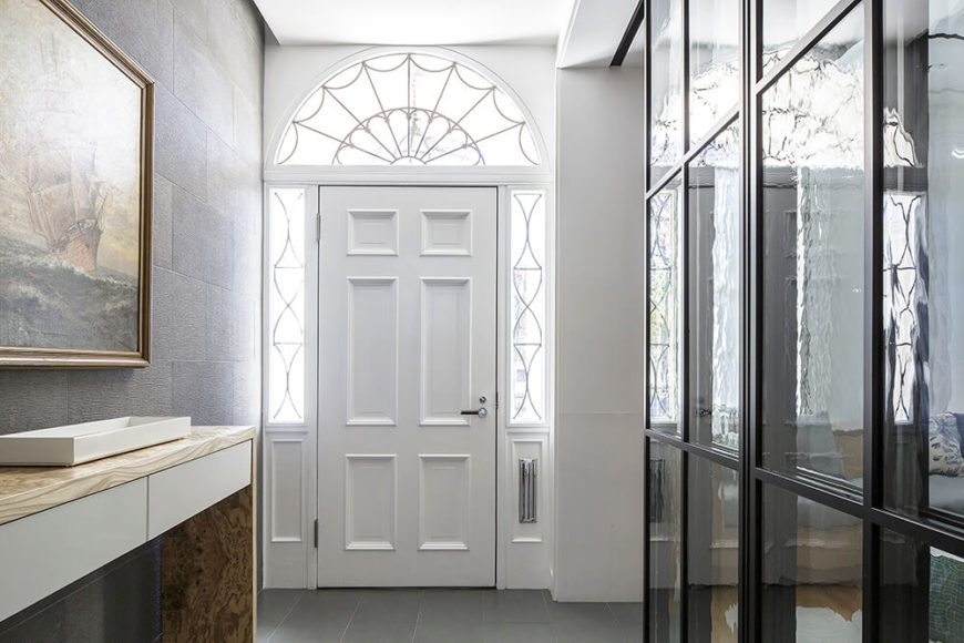 The entry way into the home is bright and well lit by natural light. Welcomed by grey tiles and golden picture frames, there is an immediate suggestion of the contrasting themes that are consistent throughout the house.