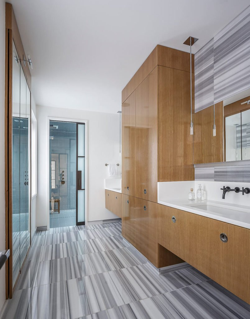 This primary bathroom features grey and white striped tile, with rich woodgrain on the cabinetry and drawers. White countertops wrap around the perimeter of the sinks, serving as a backsplash.