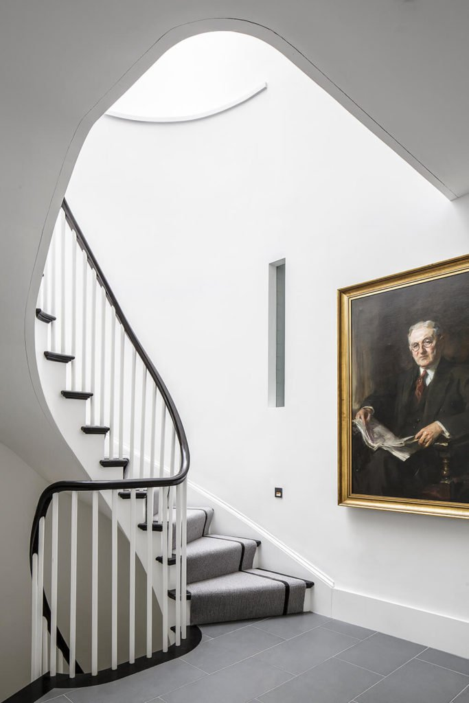 The spiral staircase leads upward, and the grey carpet covering the stairs blends seamlessly with the grey tile featured on this landing. The stark white on the walls contrasts the black trim well. A large painting is featured on the wall, contributing to the historic elements of the home.