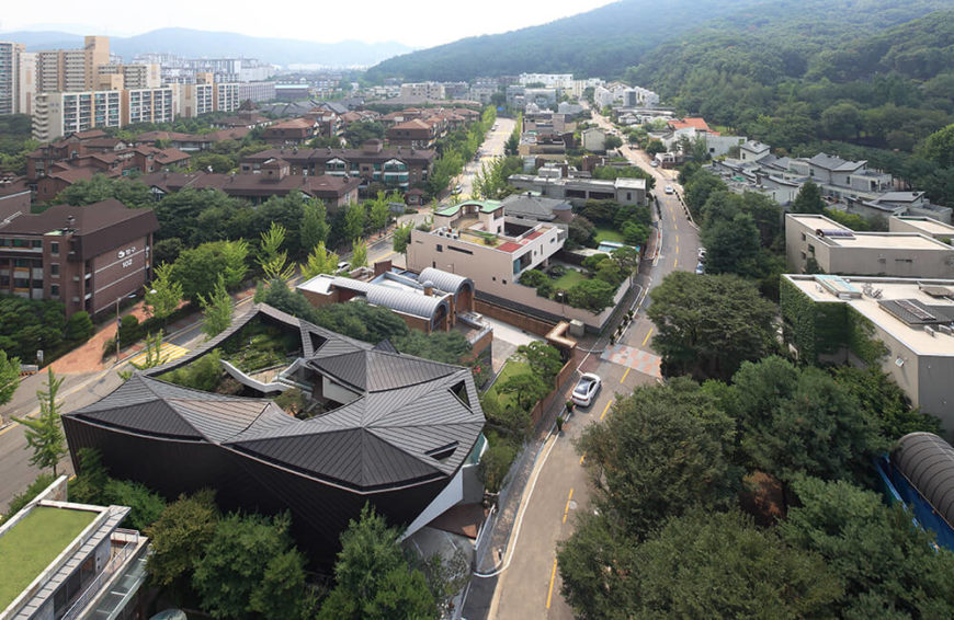 This soaring aerial view of the home and surrounding neighborhood showcases the richly forested environment the home was built in, resting at the foot of vast mountains to the right.