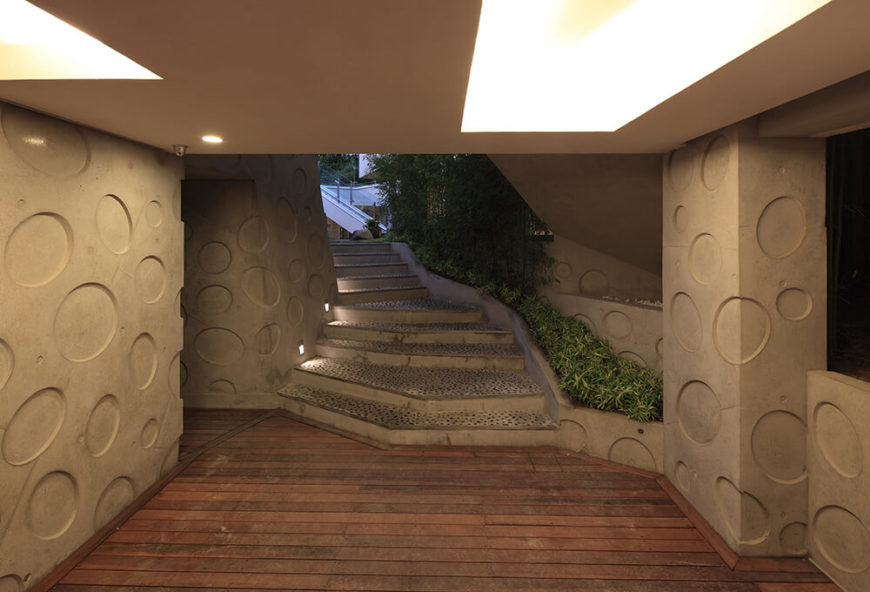 The main entryway leads down from street level to a protected patio area, surrounded by the oval patterned concrete. From here, one moves upward into and through the home.