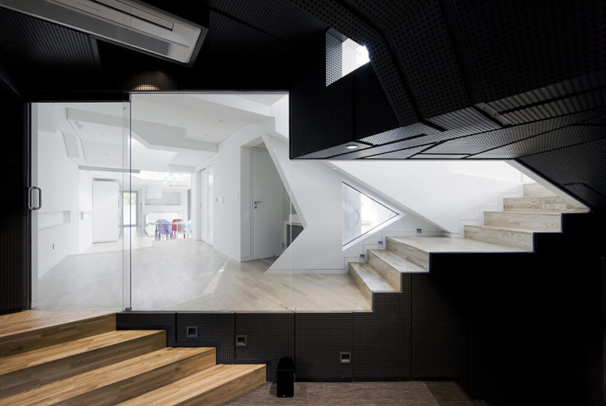 Moving back into the lower level of the home, we see a surprising change of tone, with industrial looking black panels covering the walls. This clearly delineates the lower level from the rest of the bright white and open plan home.