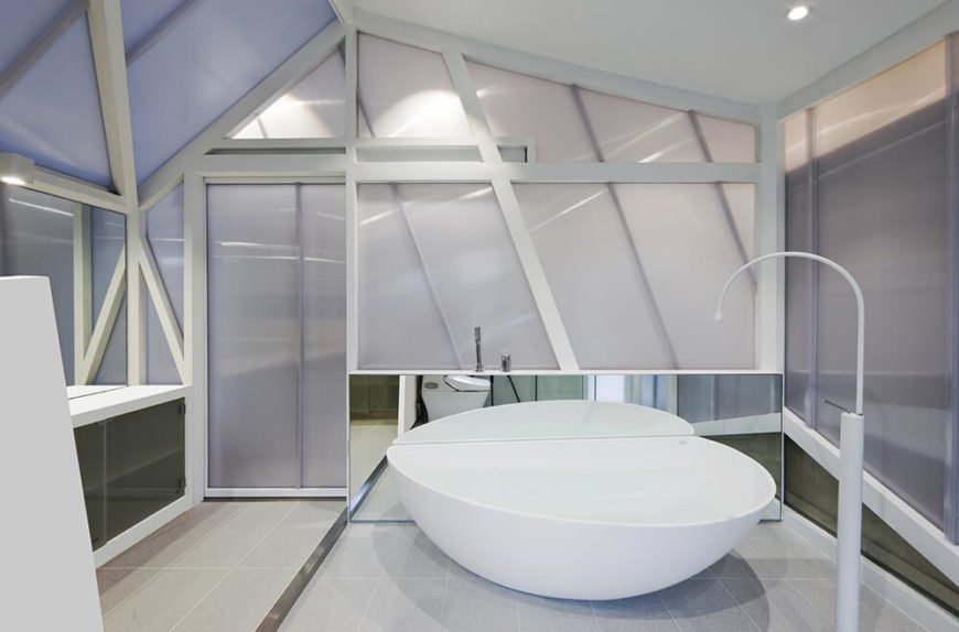 The primary bath further continues the angular, glossy look of the interior with a massive white soaking tub at center, surrounded by mirrored cabinetry and smoked glass panels.