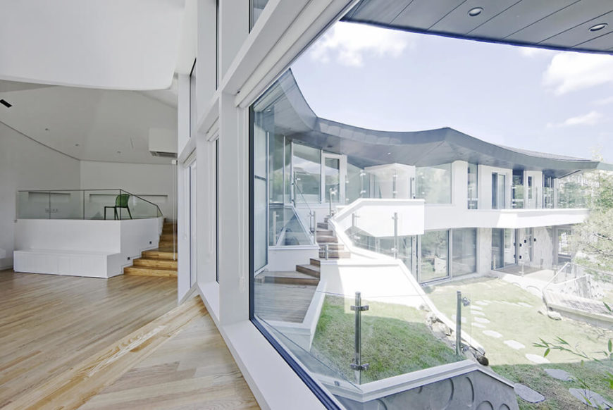 Looking out over the inner courtyard, we can see the full breadth of the home structure and its myriad windows facing the green space. The layers of stairs, balustrades, and garden features create an interlocking and visually intriguing center to the home.