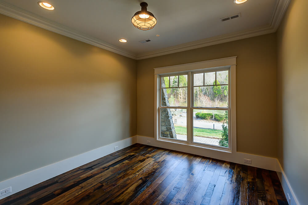 The wood floor in the study is comprised of reclaimed barn wood and is covered in a protective gloss to enhance the color variations. The large window ensure that plenty of light is let into the room.