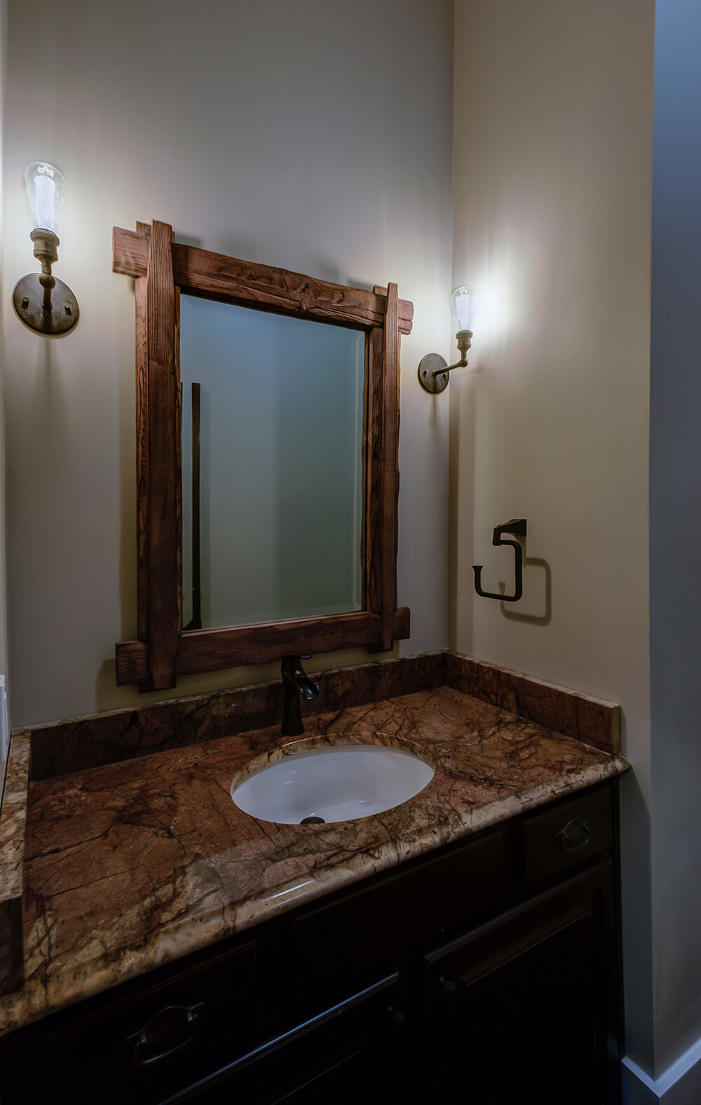 The half bath attached to the kitchen features more reclaimed barn wood around the mirror that accents the color of the countertop. The fixtures and lights of the room add to the rustic decor and highlight the wood frame well.
