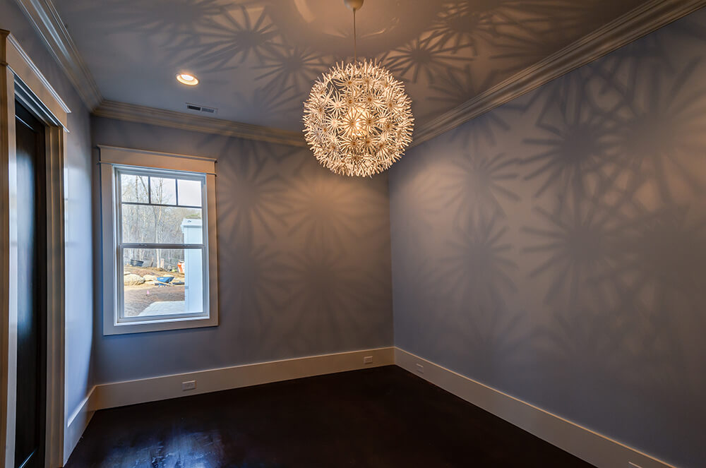 The second bedroom features a unique light fixture that casts fun shadow patterns on the walls, highlighting the powder blue paint. The use of a pale wall color helps the lighten up the room since there is only the single window.