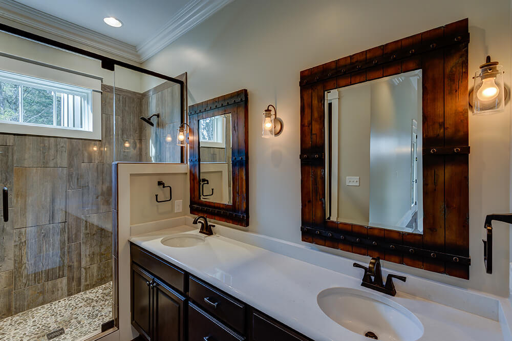 The primary bathroom features bright white counter tops, dark cabinets, and more reclaimed barn wood. Rustic touches and industrial style lights carry the decor through the room and complements the natural stone in the shower.