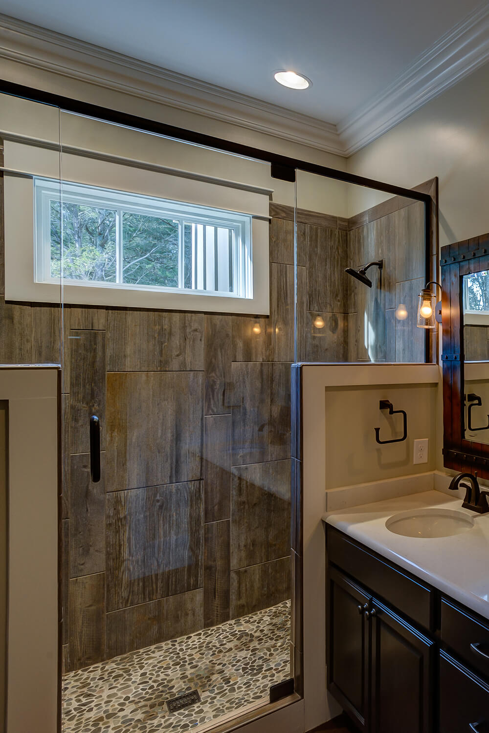 Wood finished tiles in the glass shower and a river rock floor gives this space a more rustic but luxurious feel that other rooms of the house. The river rock floor bring the stone look used around the house into this room too.