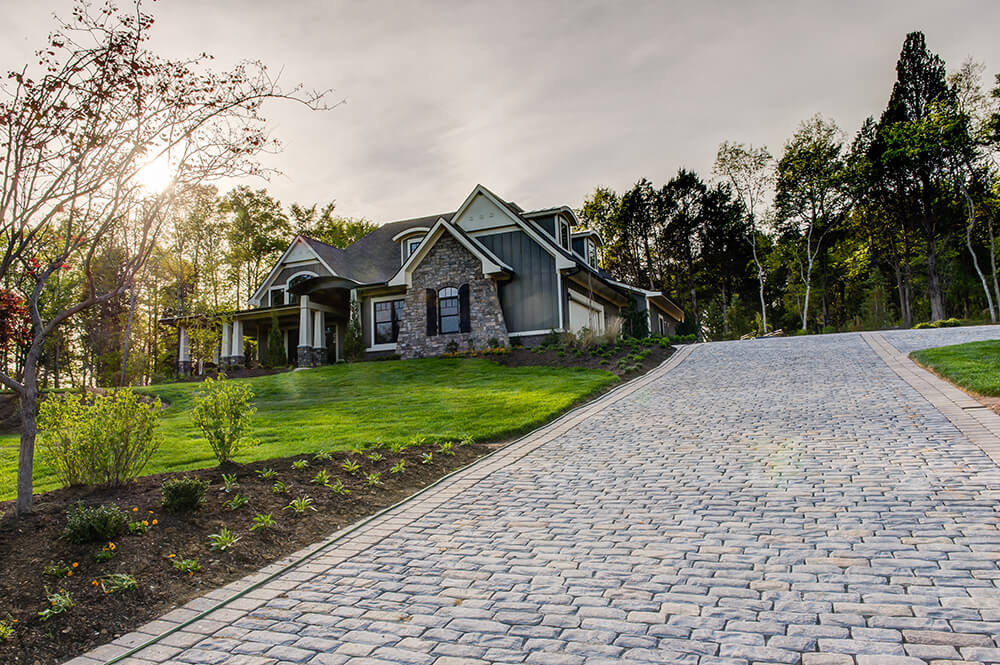 The long cobblestone driveway leads up to the garage that runs along the side of the house so as not to interrupt the front facade of the structure. The cobblestones mimic the stone seen on the house.