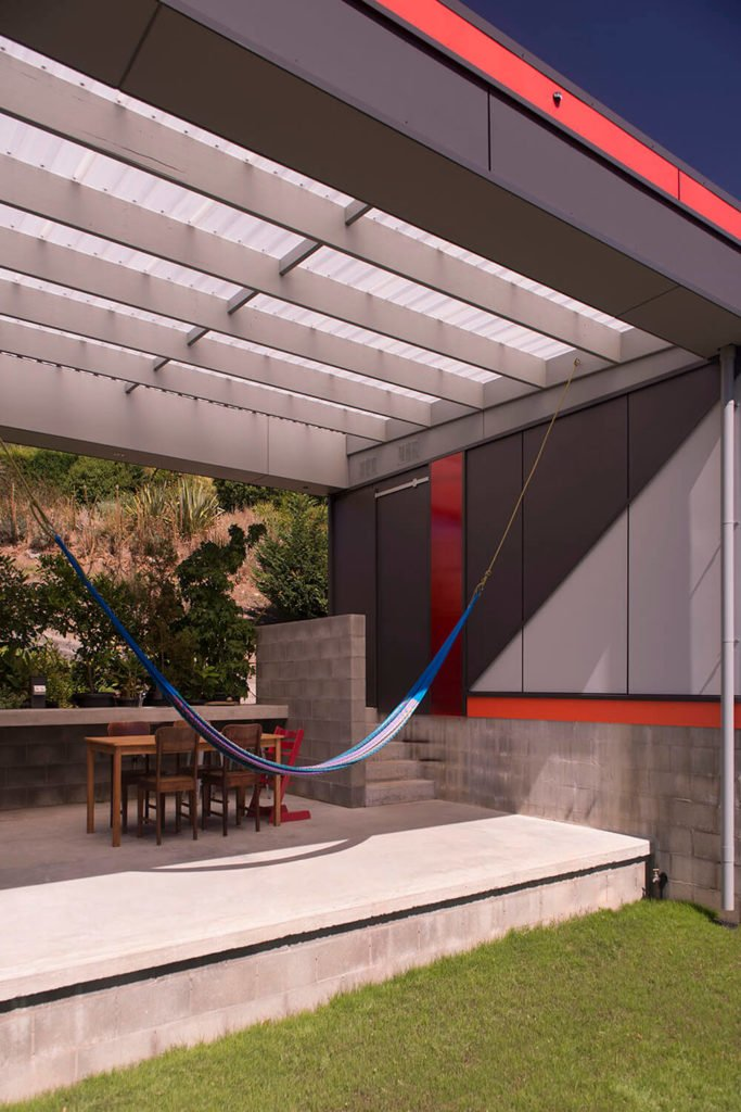 Bridging the gap between the garage and the home proper, this space provides a simple dining area, a bar, and a massive hammock suspended from the ceiling beams.