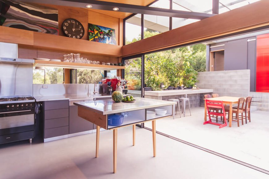 Moving inside, we see the expansive kitchen awash in stainless steel and natural wood. With the glass doors fully retracted, it's seamlessly connected to the outdoors.