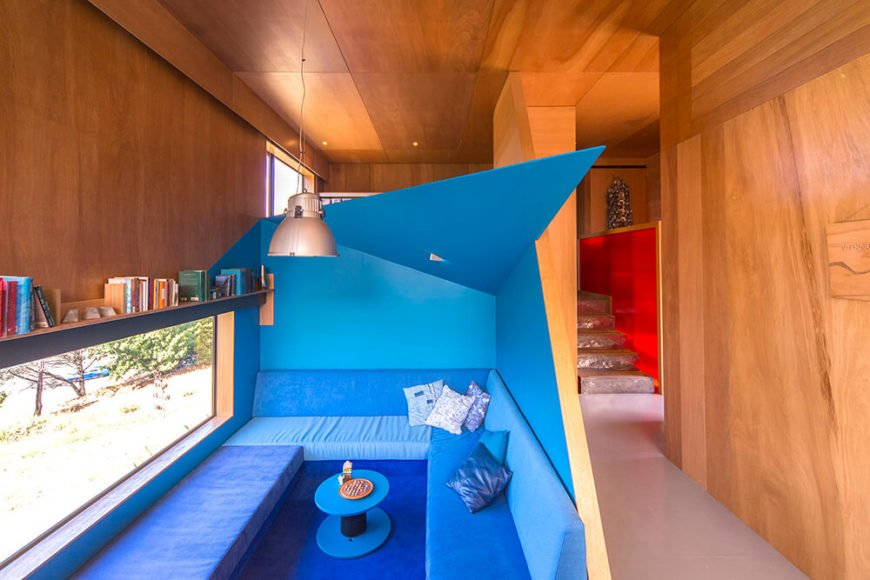 Surrounded by the rich wood paneling seen throughout the interior, this comfortable relaxing space stands out immediately with a burst of angular blue. The space is both gorgeous and useful, with a slim shelf built into the wall above the window.