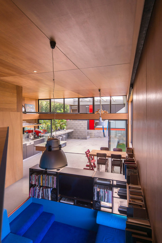 The interior spreads out in a massive open plan design, connecting living, dining, and kitchen spaces within the same large room. With those retractible doors open, this space blurs into the outdoors as well.