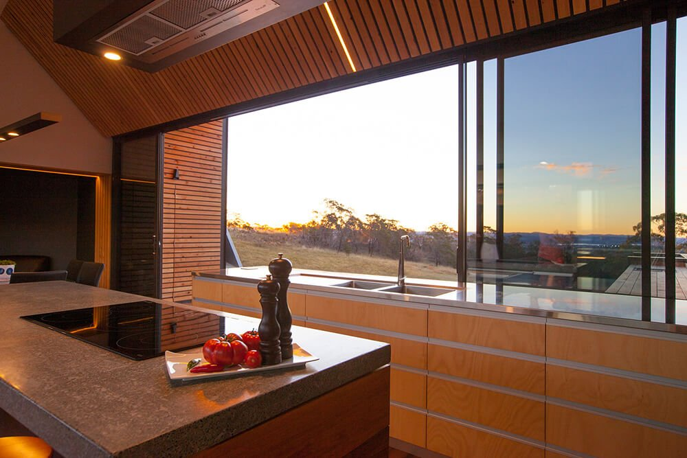 A focused shot at this galley kitchen's glass window overlooking the beautiful surroundings around the property.