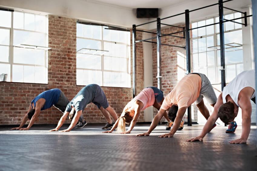 Yoga studio design with brick walls, large windows and dark floor.