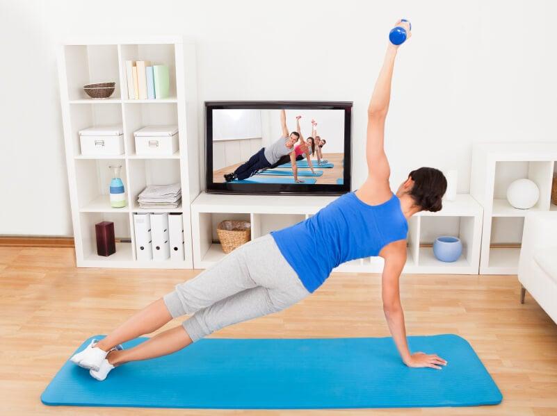 Doing yoga in living room watching yoga DVD