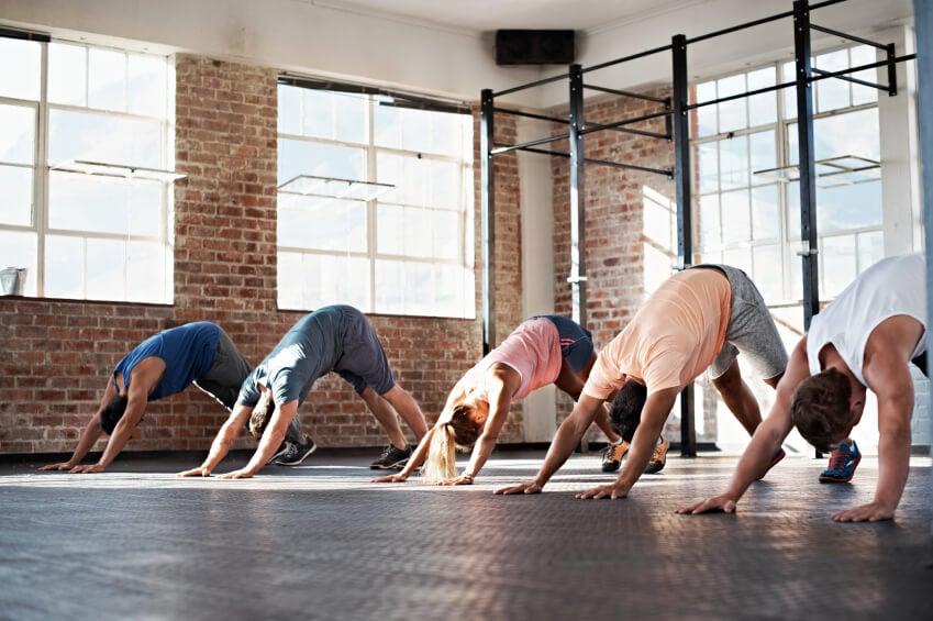 Yoga studio with brick walls, large windows and dark floor.