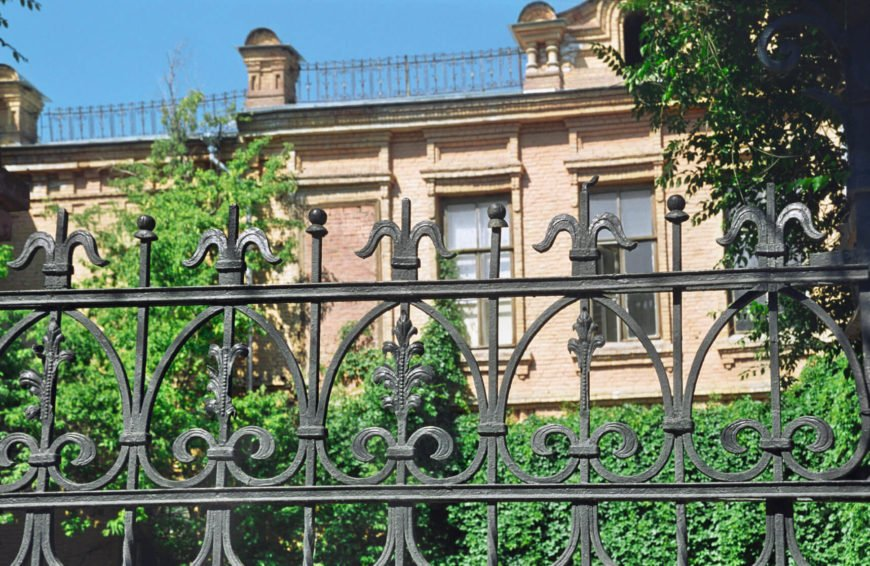 Classic wrought iron fence in front of a hedge garden.