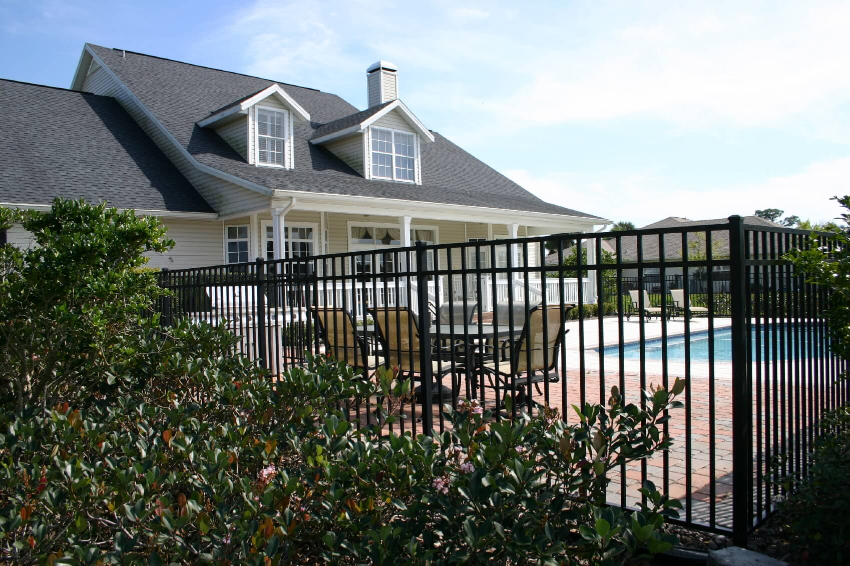 Lovely black wrought iron fence surrounding a backyard pool complex.