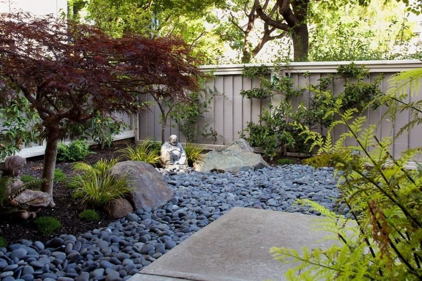 A beige vinyl fence with shutter-like slats. The color easily meshes with this Japanese style Zen garden, which usually feature bamboo fences.