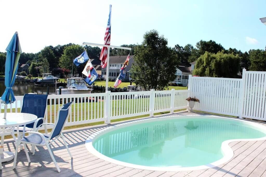 White vinyl or wood bar style pool fence gives a clean breezy and bright look to this deck and pool area.