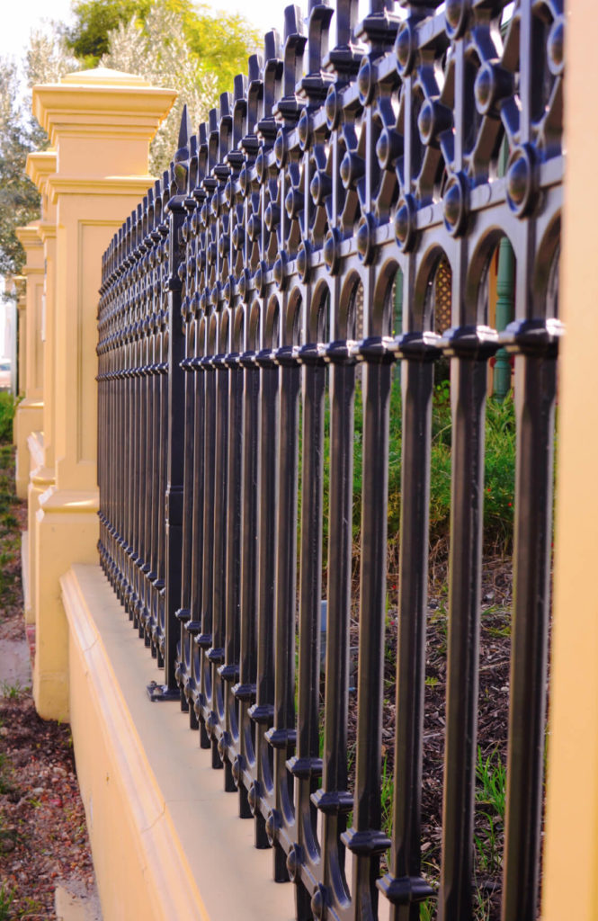 A classic wrought iron design is incorporated into this mixed material fence.