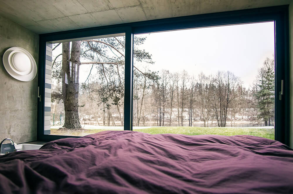 One of the large guest bedrooms is on the ground level facing the river. The floor to ceiling windows double as doors out to the small patio.