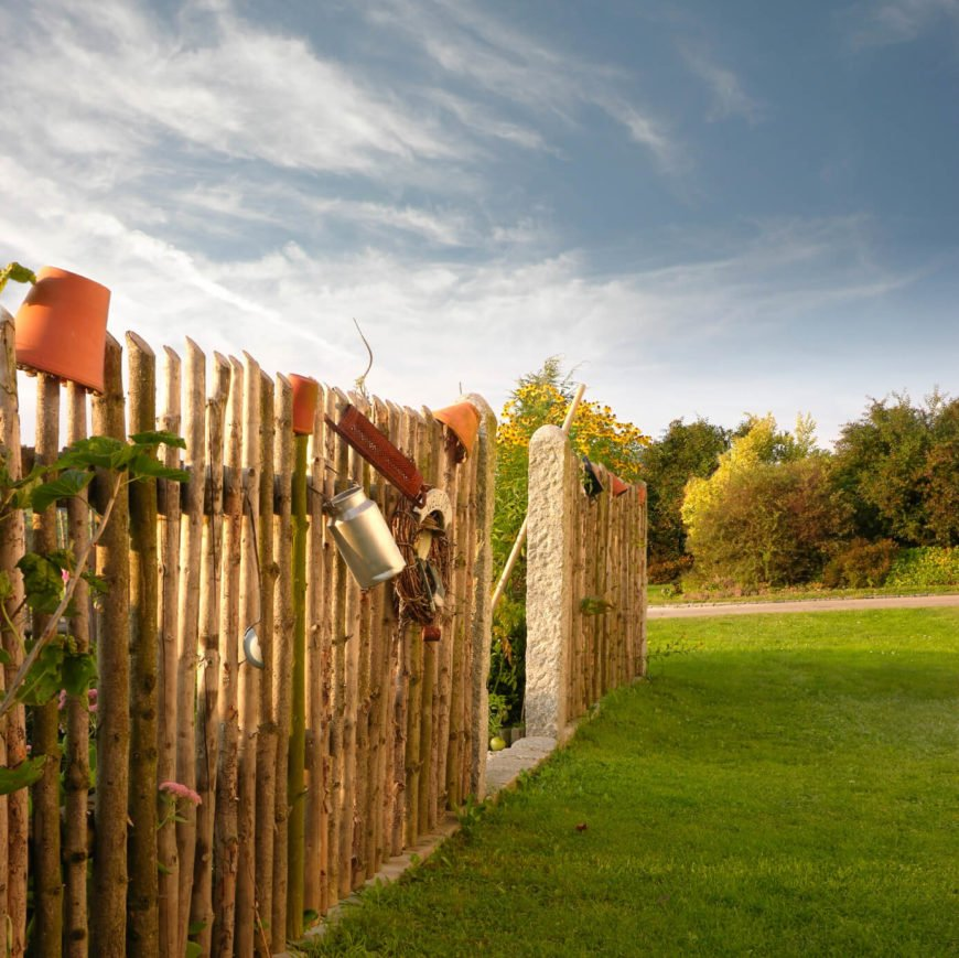 A natural stick fence with vines crawling up the posts.
