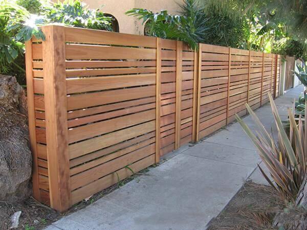 A horizontal slat fence with varying sized slats.
