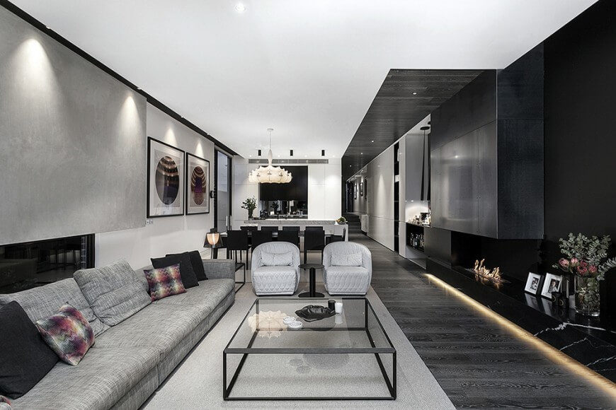 Two round backed club chairs make comfy additional seating in this modern and sleek living room.