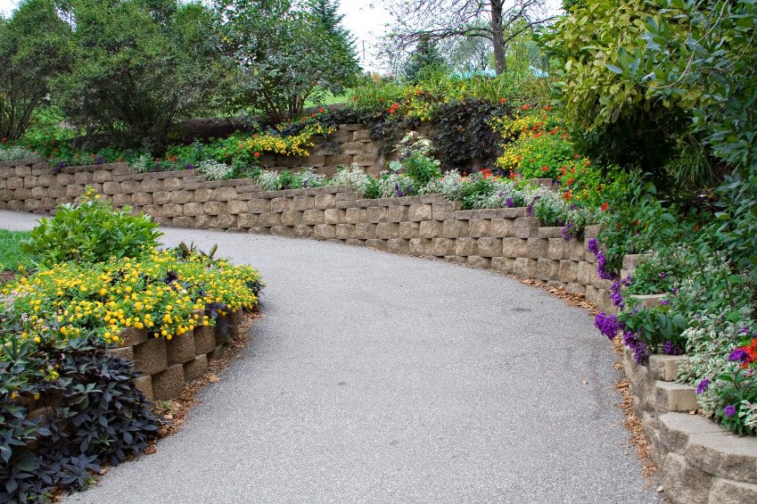This winding retaining wall is made out of stacked stone bricks and is decorated with flowers and plants all the way up.