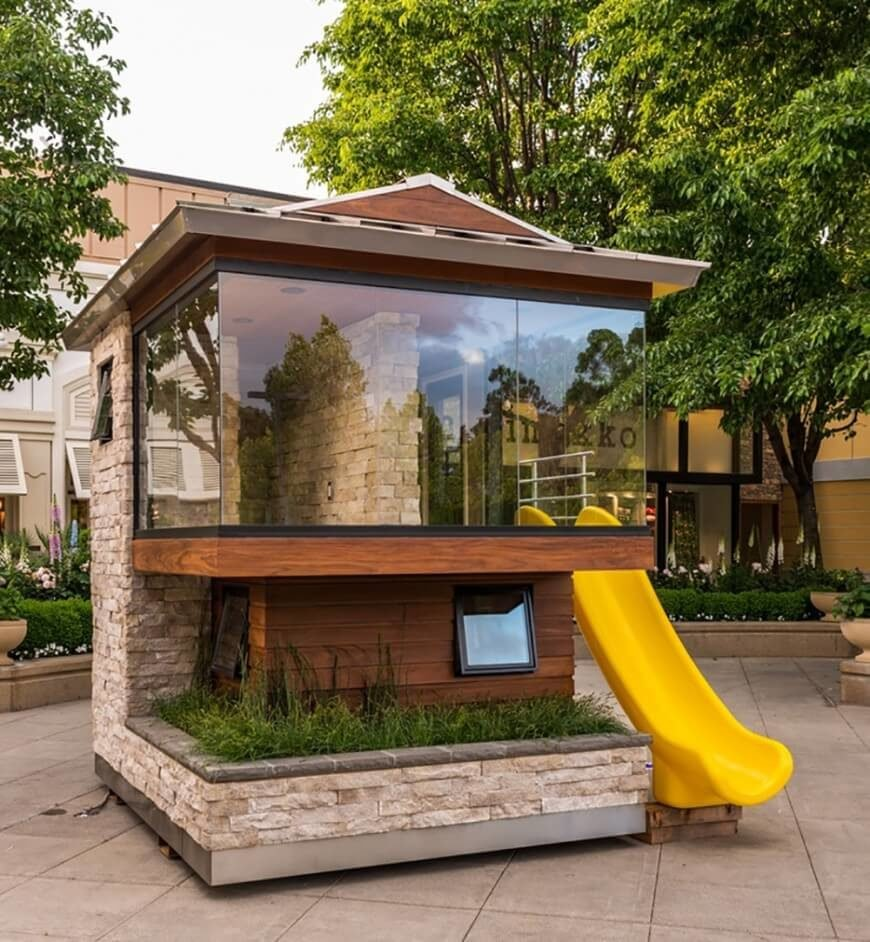 A much more modern playground with a glass window and a slide