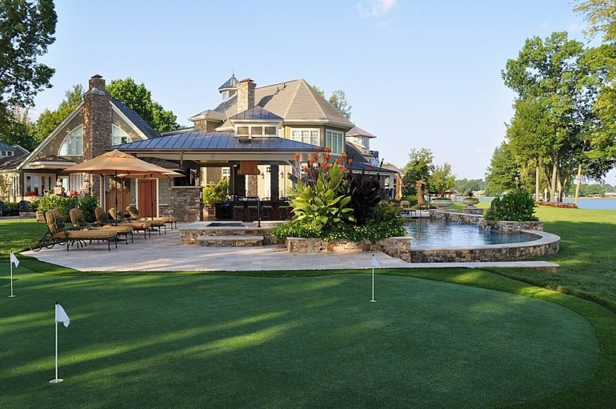 A large putting green placed just beyond the pool and a large patio complete with a covered bar area.