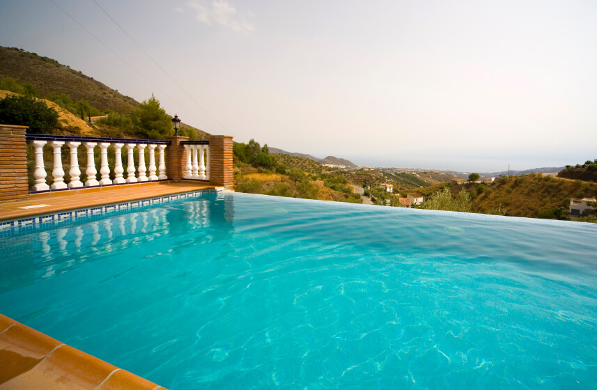 An interesting brick and pillar barrier acts as a pool fence surrounding this infinity pool.
