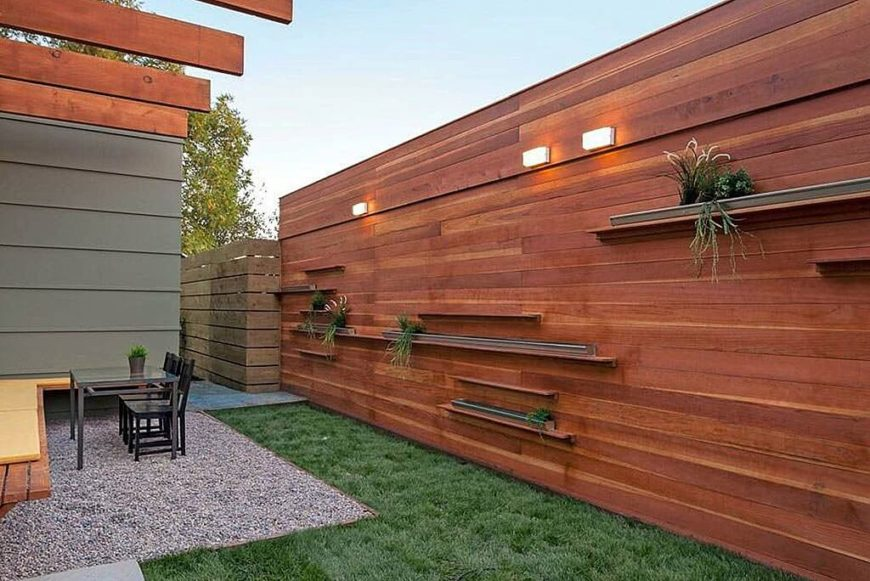 A tall fence that incorporates shelves and lights into the design.